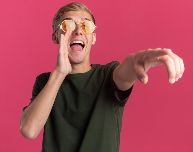 Radosny młody przystojny facet w zielonej koszuli i okularach wskazuje na bok i dzwoni do kogoś odizolowanego na różowej ścianie