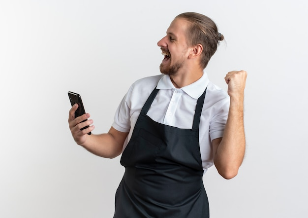 Radosny młody przystojny fryzjer na sobie mundur trzymając telefon komórkowy i podnosząc pięść z zamkniętymi oczami na białym tle