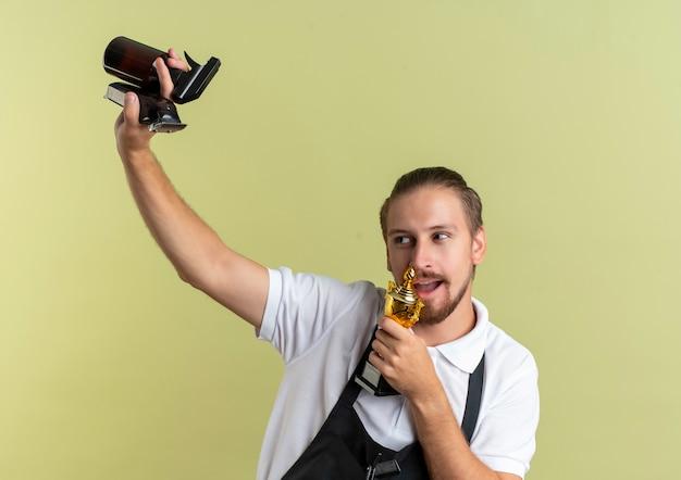 Radosny młody przystojny fryzjer podnoszący maszynkę do strzyżenia włosów, butelkę z rozpylaczem i udawaj śpiewanie, używając kubka zwycięzcy jako mikrofonu, patrząc na bok odizolowany na oliwkowej zieleni