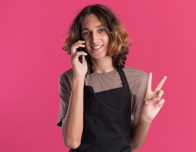 Radosny młody przystojny fryzjer ubrany w mundur, patrzący z przodu, rozmawiający przez telefon, robiący znak pokoju na różowej ścianie z kopią miejsca
