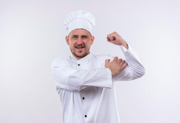 Radosny młody przystojny kucharz w mundurze szefa kuchni, gestykulując mocno i kładąc rękę na ramieniu na białym tle na białej ścianie