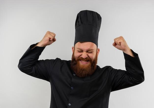 Radosny młody przystojny kucharz w mundurze szefa kuchni, podnoszący pięści z zamkniętymi oczami na białym tle na białej ścianie