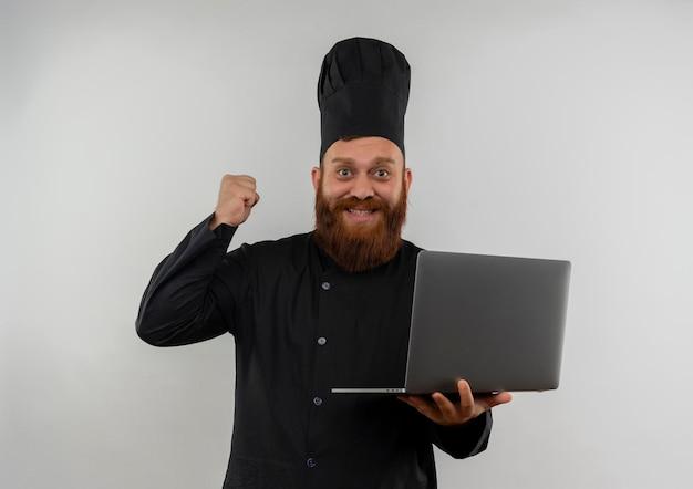 Radosny młody przystojny kucharz w mundurze szefa kuchni trzymający laptopa i podnoszący pięść na białym tle na białej ścianie