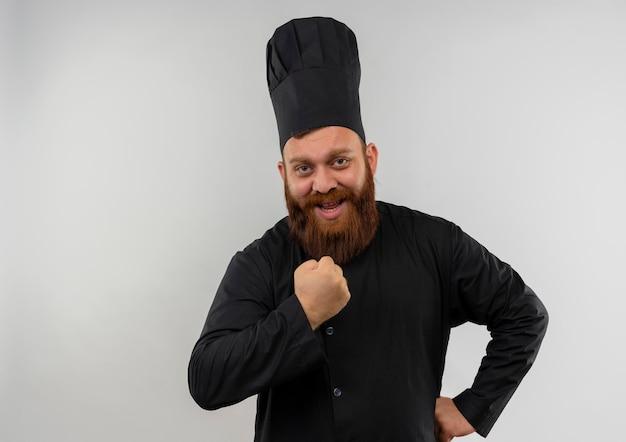 Radosny młody przystojny kucharz w mundurze szefa kuchni, zaciskając pięść i kładąc rękę na talii na białym tle na białej ścianie z miejscem na kopię