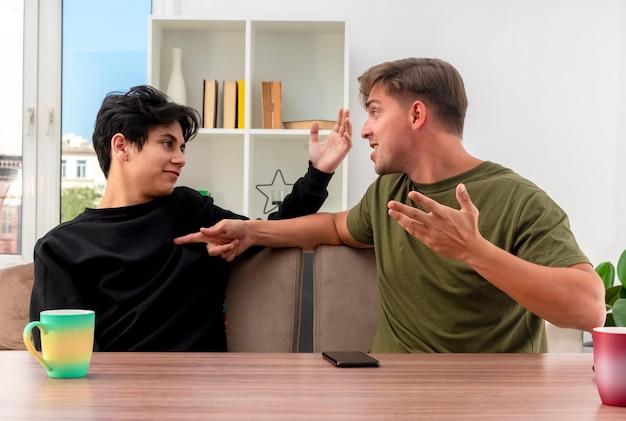 Radosny młody przystojny mężczyzna blondynka siedzi przy stole patrząc i wskazując na zadowolony młody przystojny chłopak brunetka, podnosząc rękę