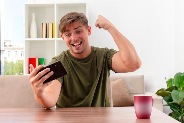 Radosny młody przystojny mężczyzna blondynka siedzi przy stole z filiżanką, podnosząc pięść i patrząc na telefon w salonie