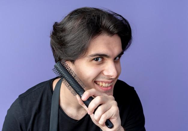 Radosny młody przystojny mężczyzna fryzjer w mundurze trzymając grzebień na białym tle na niebieskiej ścianie