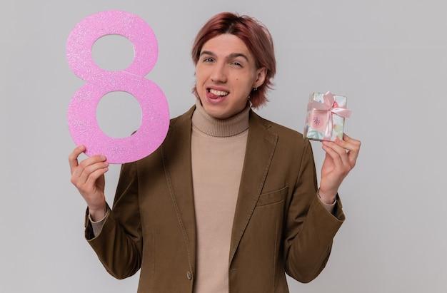Radosny młody przystojny mężczyzna trzyma różowy numer osiem i pudełko upominkowe