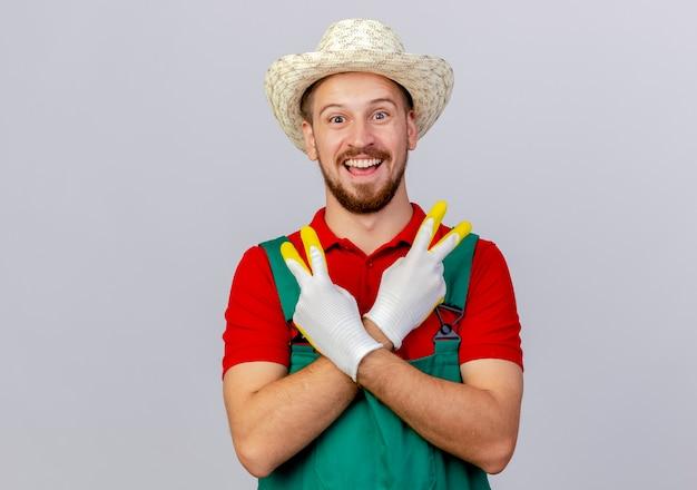 Radosny młody przystojny ogrodnik słowiański w mundurze na sobie rękawiczki ogrodnicze i kapelusz patrząc, trzymając ręce skrzyżowane robi znak pokoju na białym tle