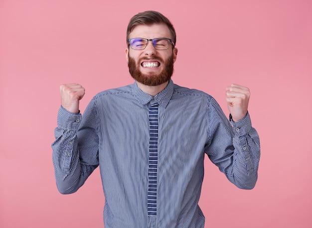 Radosny młody przystojny rudy brodacz w okularach i bluzce w paski, stoi na różowym tle, zaciska pięści, szeroko się uśmiecha i jest absolutnie szczęśliwy - wygrał na loterii!
