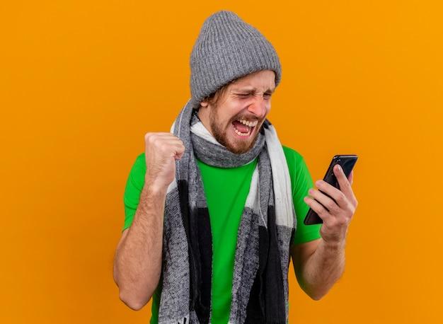 Radosny młody przystojny słowiański chory mężczyzna w czapce zimowej i szaliku, trzymając i patrząc na telefon komórkowy robi gest tak na białym tle na pomarańczowej ścianie z miejsca na kopię