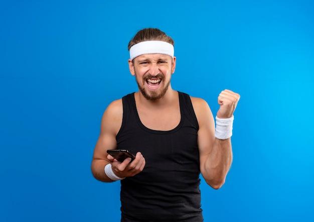 Radosny młody przystojny sportowy mężczyzna nosi opaskę i opaski, trzymając telefon komórkowy i zaciskając pięść na białym tle na niebieskiej ścianie z miejsca na kopię