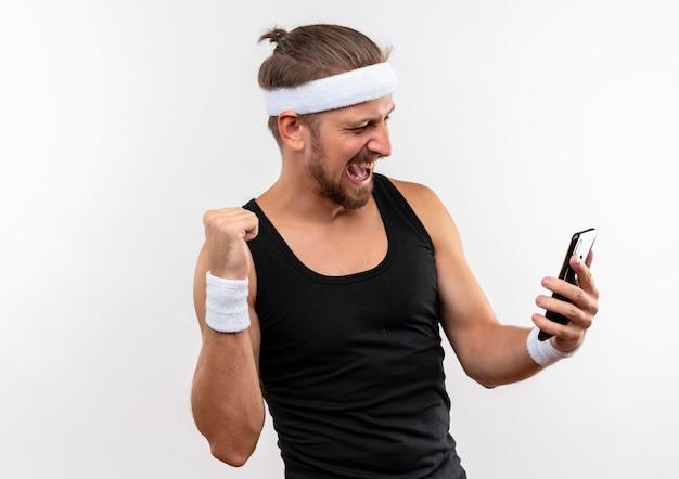 Radosny młody przystojny sportowy mężczyzna nosi opaskę i opaski trzymając telefon komórkowy, patrząc na niego i zaciskając pięść na białym tle na białej ścianie