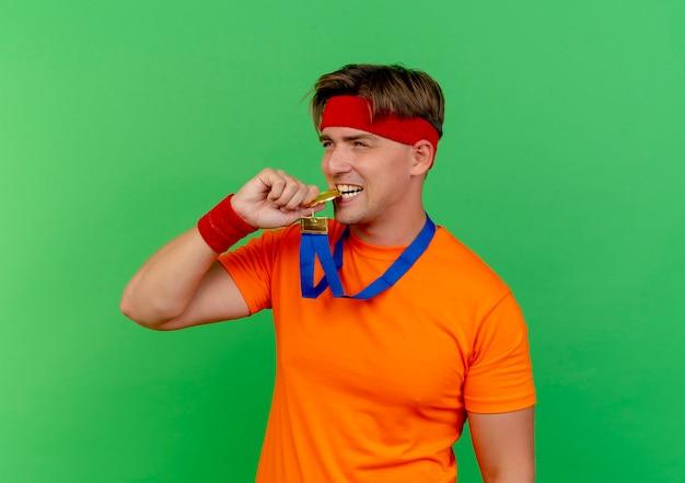 Radosny młody przystojny sportowy mężczyzna ubrany w opaskę i opaski na rękę z medalem wokół szyi, gryzący medal i patrząc prosto na zielono