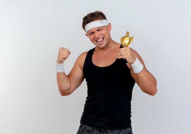 Radosny młody przystojny sportowy mężczyzna w opasce i opaskach na rękę trzyma puchar zwycięzcy i zaciśniętą pięść z zamkniętymi oczami odizolowanymi na białym