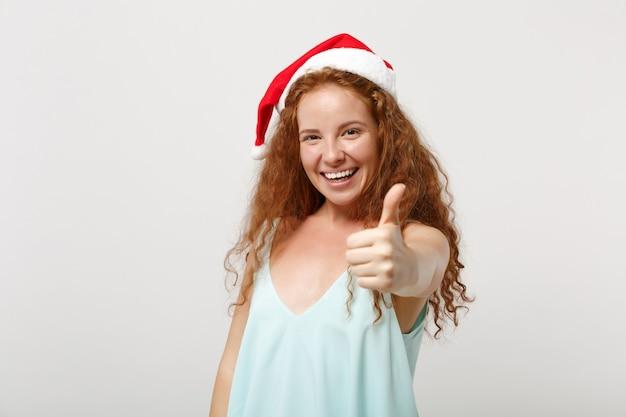 Radosny młody rudy santa dziewczyna w lekkie ubrania, boże narodzenie kapelusz na białym tle na białym tle, portret. szczęśliwego nowego roku 2020 celebracja wakacje koncepcja. makieta miejsca na kopię. pokazuje kciuk w górę.