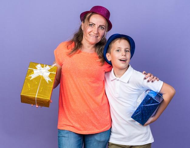 Radosny młody słowiański chłopiec w niebieskim kapeluszu imprezowym trzymający pudełka z prezentami z matką w fioletowym kapeluszu imprezowym odizolowanym na fioletowej ścianie z kopią miejsca