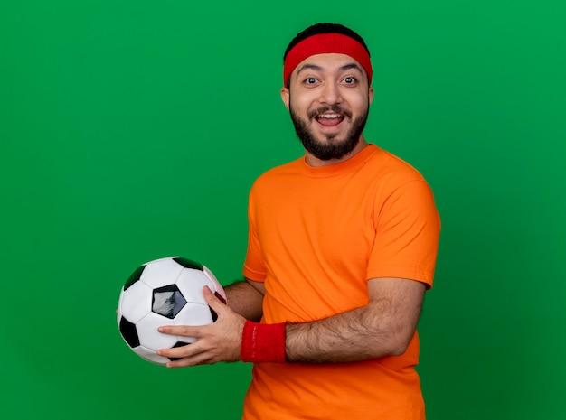 Radosny młody sportowy człowiek ubrany w opaskę i opaskę trzyma piłkę z boku na białym tle na zielono
