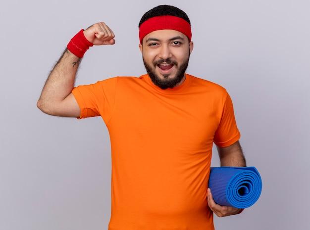 Radosny młody sportowy mężczyzna ubrany w opaskę i opaskę trzyma matę do jogi, pokazując silny gest na białym tle