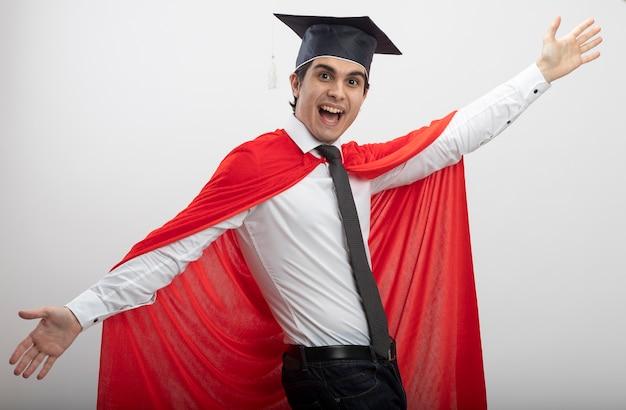 Radosny młody superbohater facet patrząc na kamery na sobie krawat i kapelusz absolwenta, rozkładając ręce na białym tle