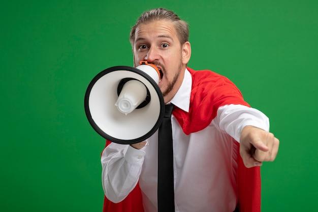 Radosny młody superbohater facet w krawacie mówi przez głośnik i pokazuje gest na białym tle na zielonym tle