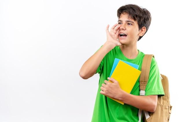 Radosny młody szkolny chłopiec noszący plecak trzymający książki, dzwoniący do kogoś odizolowanego na białej ścianie z miejscem na kopię