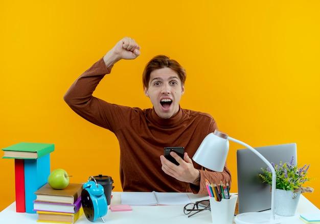 Radosny młody uczeń chłopiec siedzi przy biurku z narzędzi szkolnych, trzymając telefon i podnosząc rękę