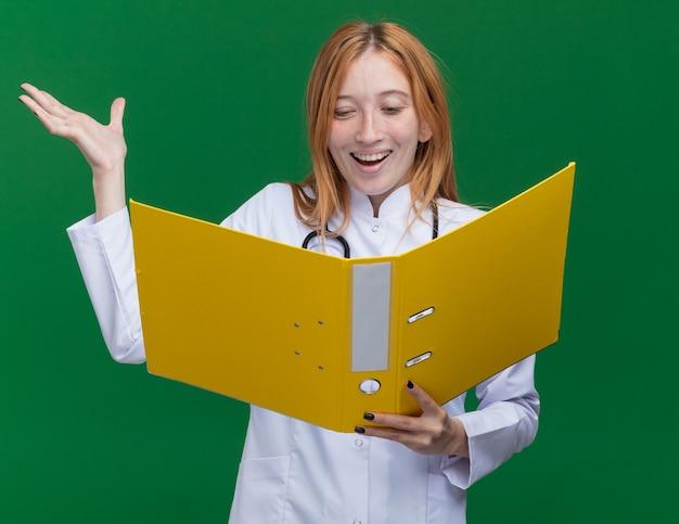 Radosny młody żeński lekarz imbir nosi szatę medyczną i stetoskop, trzymając i patrząc na folder pokazujący pustą rękę odizolowaną na zielonej ścianie