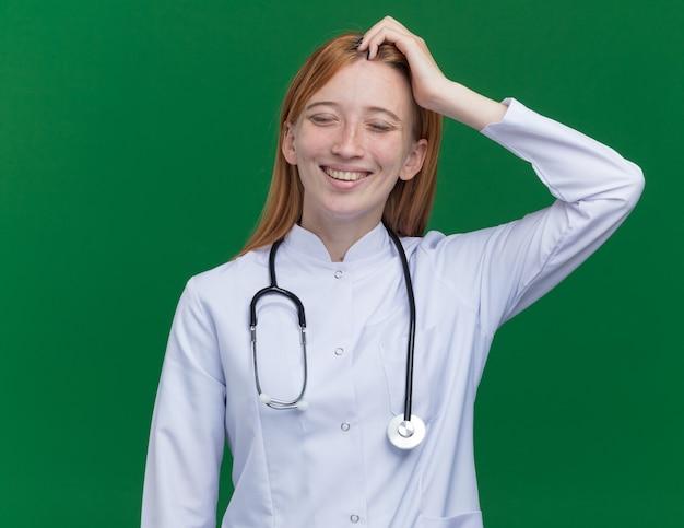 Radosny młody żeński lekarz imbirowy ubrany w szatę medyczną i stetoskop dotykający głowy uśmiechający się z zamkniętymi oczami odizolowanymi na zielonej ścianie