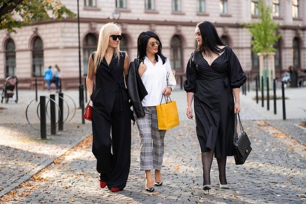 Radosny model uśmiechnięte przyjaciółki dobrze się bawią po zakupach. grupa młodych ludzi spacerujących po parku. przyjaciele zabawy.