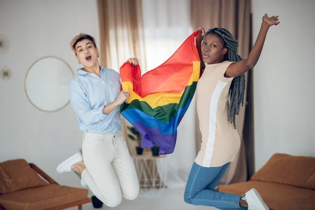 Radosny nastrój. dwie młode dziewczyny trzymając tęczową flagę i skoki