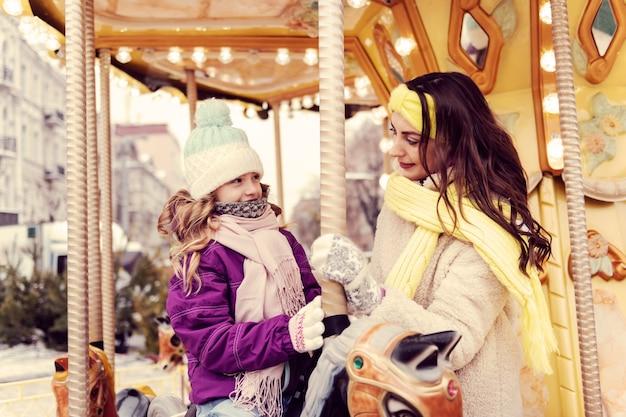 Radosny nastrój. młoda brunetka stoi w pozycji pół i spędza czas w parku rozrywki