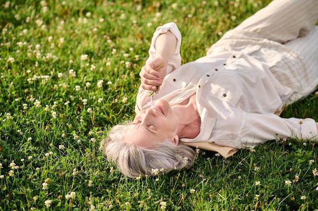 Radosny nastrój. optymistyczna kobieta z siwymi włosami w jasnym garniturze leżąca na trawie patrząca na kwiatek w letni dzień