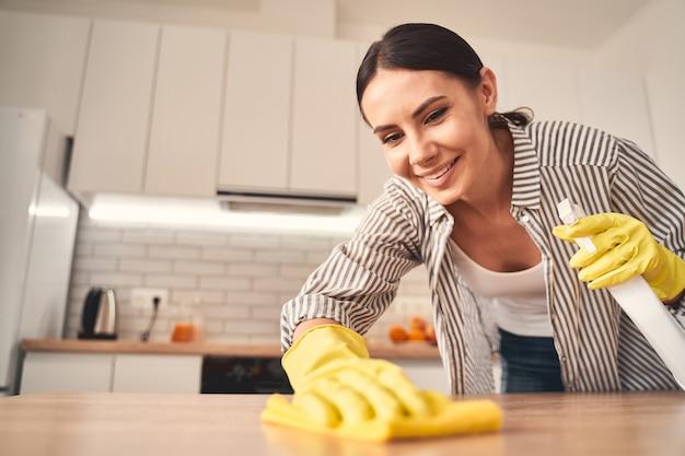 Radosny nastrój. śliczna kobieta wyrażająca pozytywne nastawienie podczas wycierania stołu przed rozpoczęciem pracy na odległość