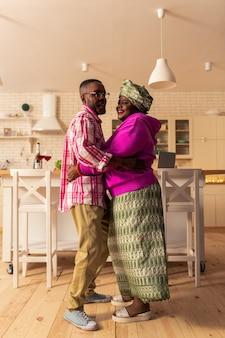 Radosny nastrój. zachwycona szczęśliwa para uśmiecha się podczas tańca w domu