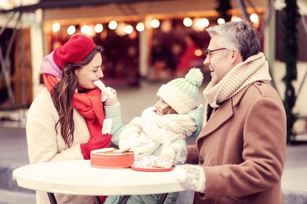 Radosny nastrój. zadowolony mężczyzna wyrażający pozytywne nastawienie słuchając swoich dziewczyn