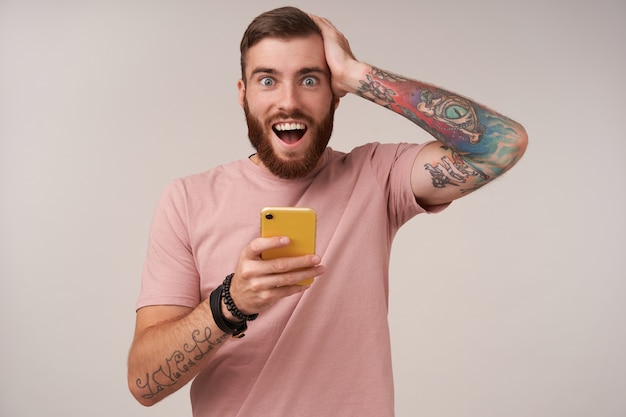Radosny, niebieskooki młody nieogolony mężczyzna z tatuażami ściskającymi głowę z podniesioną ręką z zaskoczoną twarzą, odizolowany na białym