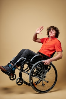 Radosny niepełnosprawny facet na wózku inwalidzkim przywitaj się, uśmiechnięty, baw się sam, odizolowany portret