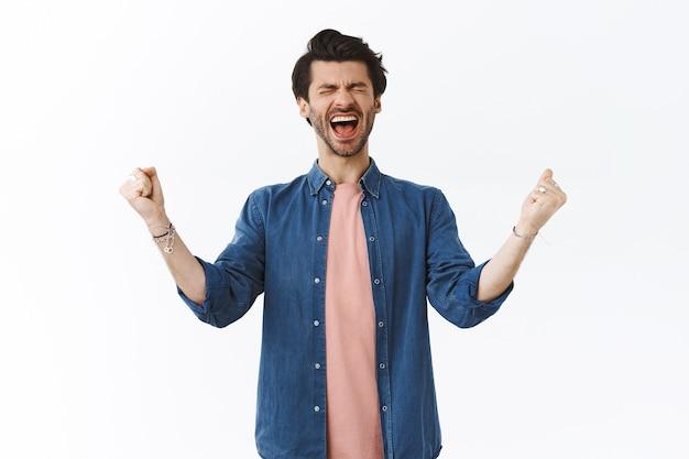 Radosny niezwykle szczęśliwy przystojny brodaty facet krzyczy ze szczęścia głośno, zamyka oczy i zaciska pięści, podnosi ręce z radości, wygrywa uczucie szczęścia, triumfuje, świętuje niesamowite zwycięstwo