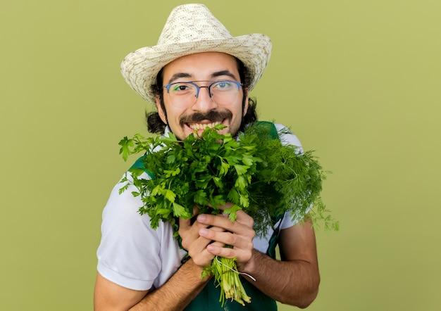 Radosny ogrodnik męski w okularach optycznych w kapeluszu ogrodniczym trzyma koper i kolendrę