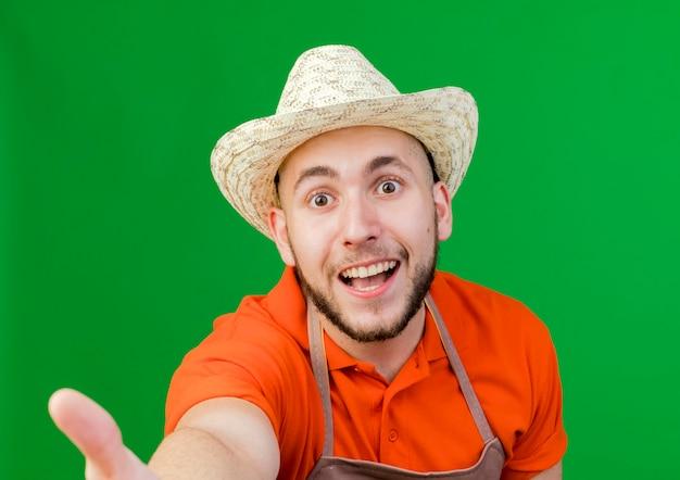 Radosny ogrodnik mężczyzna w kapeluszu ogrodniczym udaje, że trzyma i patrzy