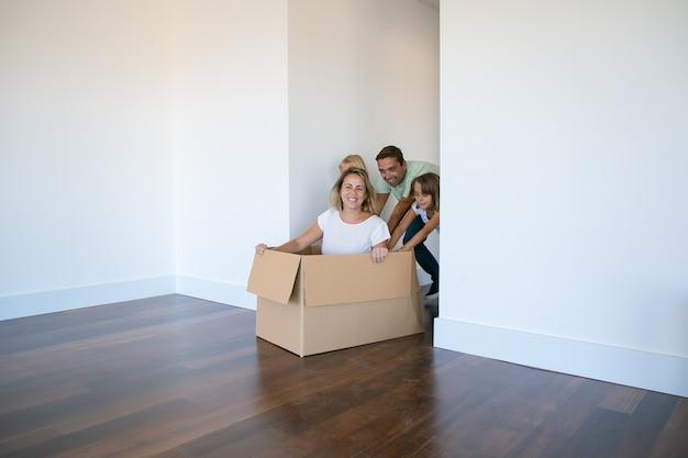 Radosny ojciec i dwie córki pchają mamę w kartonowym pudełku