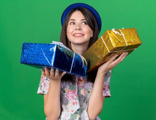 Radosny patrząc z boku młoda piękna dziewczyna w kapeluszu imprezowym, trzymająca pudełka na prezenty