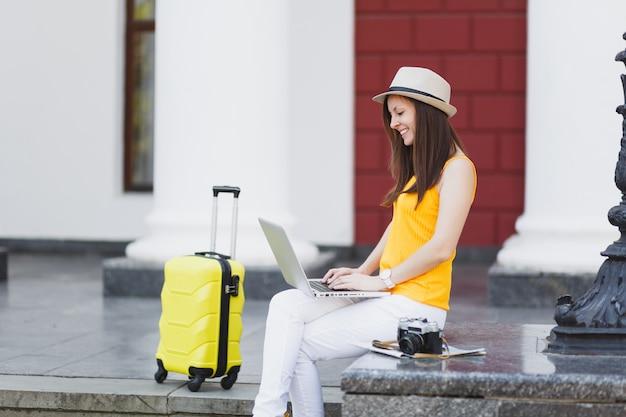 Radosny podróżnik turysta kobieta w ubraniach casual, kapelusz z walizką siedzi za pomocą pracy na komputerze typu laptop pc w mieście na świeżym powietrzu. dziewczyna wyjeżdża za granicę na weekendowy wypad. styl życia podróży turystycznej.