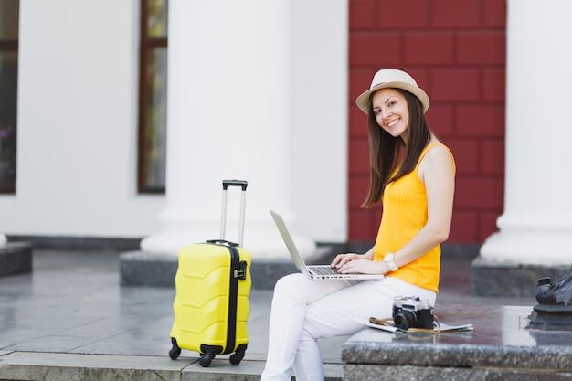 Radosny podróżnik turysta kobieta w ubranie, kapelusz z walizką siedzieć przy pracy na komputerze typu laptop w mieście na świeżym powietrzu. dziewczyna wyjeżdża za granicę na weekendowy wypad. styl życia podróży turystycznej.