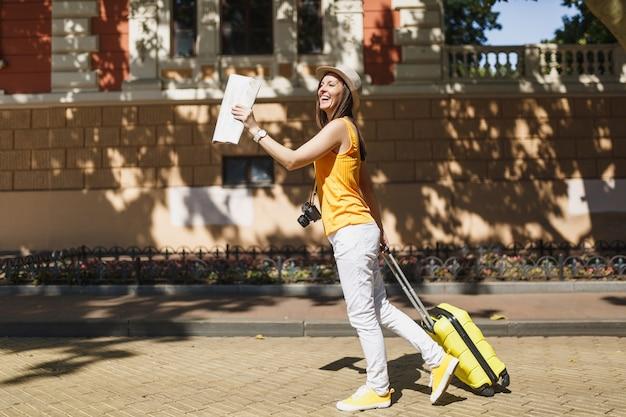 Radosny podróżnik turystyczny kobieta w żółtym letnim kapeluszu na co dzień ubrania z mapą miasta walizka chodzenie po mieście na świeżym powietrzu. dziewczyna wyjeżdża za granicę na weekendowy wypad. koncepcja życia podróż turystyka.