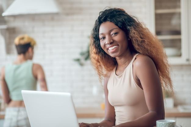 Radosny poranek. młoda uśmiechnięta amerykańska kobieta na laptopa i dziewczyna stoi zajęty na odległość w kuchni