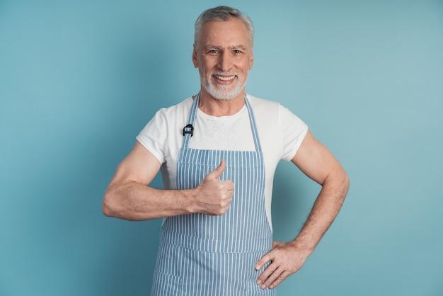 Radosny, pozytywny emeryt pokazuje kciuki do góry i nosi fartuch