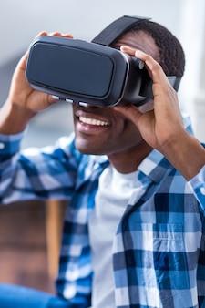 Radosny pozytywny młody człowiek uśmiecha się i trzyma okulary 3d podczas korzystania z technologii wirtualnych