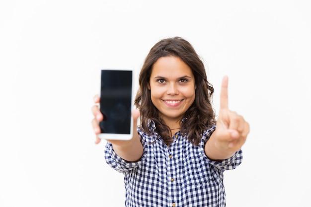 Radosny pozytywny użytkownik telefonu komórkowego pokazuje pustego ekran